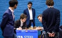 Коллеги по цеху обступили игровой стол за которым играли Магнус Карлсен и Гавейн Джонс