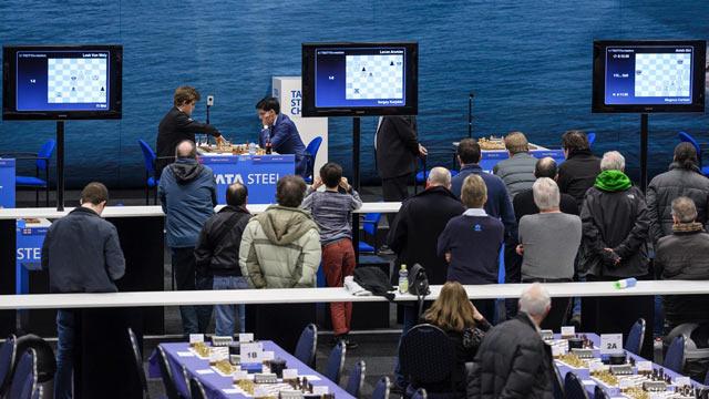 Взгляд из общей игровой зоны, в которой играют шахматисты -любители. На дальнем плане сражаются Магнус Карлсен и Аниш Гири