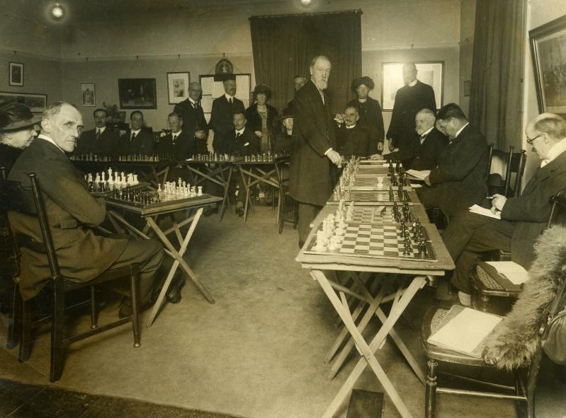 Джозеф Блэкберн проводит сеанс одновременной игры на 20 досках против членов императорского шахматного клуба (Лондон, 1921)