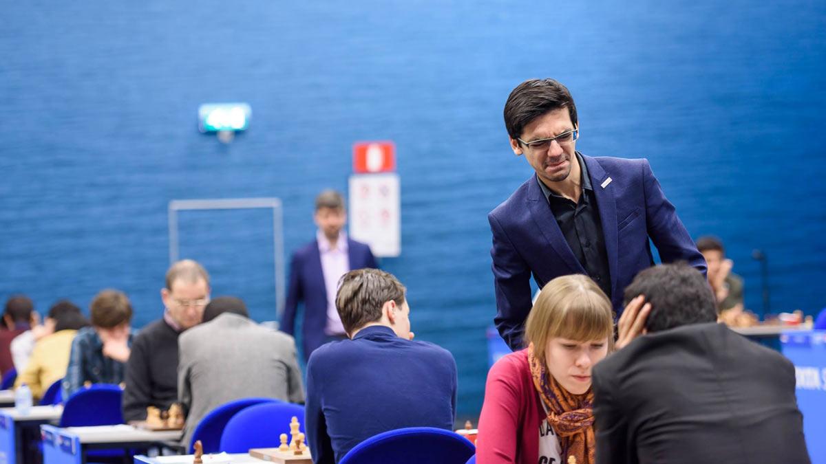 Аниш Гири наблюдает за игрой участников Tata Steel Challengers Ольги Гири и Видита Сантоша. Судя по выражению лица Аниша, он уже понял, что дела у Ольги идут не очень...