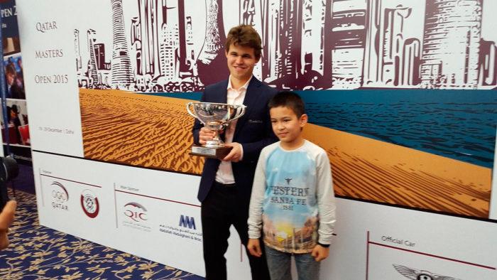 Магнус Карлсен с кубком Qatar Masters Open 2015 и Нодирбек Абдусатторов | Доха (Катар), 2015