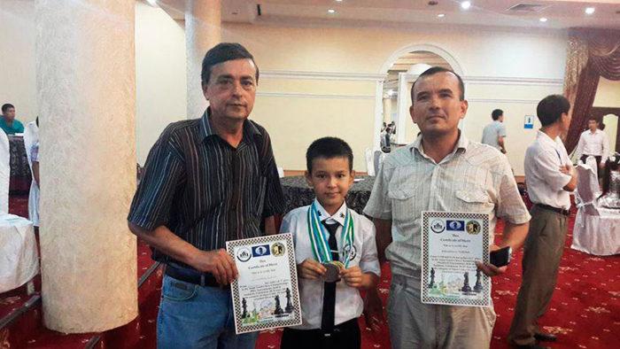 Слева направо: Дмитрий Каюмов — тренер Абдусатторова, Нодирбек и его отец Фазлиддин